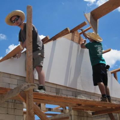 Teenage volunteers doing building work in the Philippines work on a structure's roof
